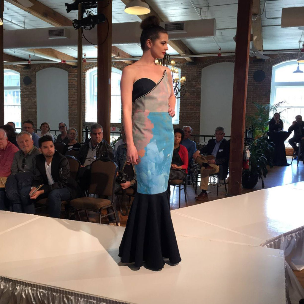 Model on runway wearing a mermaid style black, light blue, and tan colored dress.