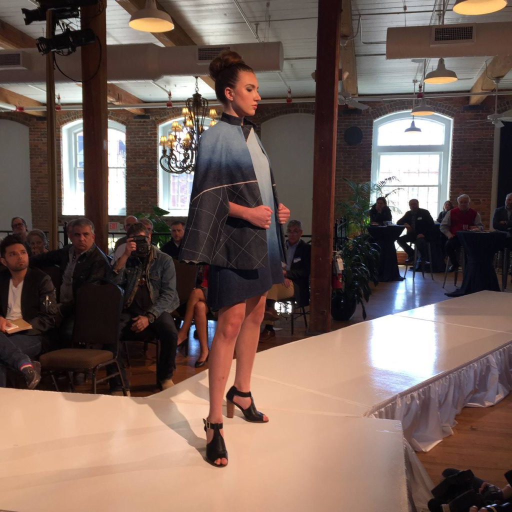 Model on runway wearing blue and black dress with matching jacket