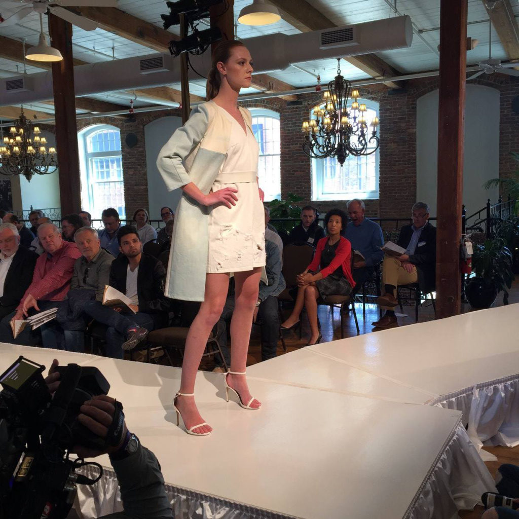 Model on runway wearing white minidress and a light blue jacket.