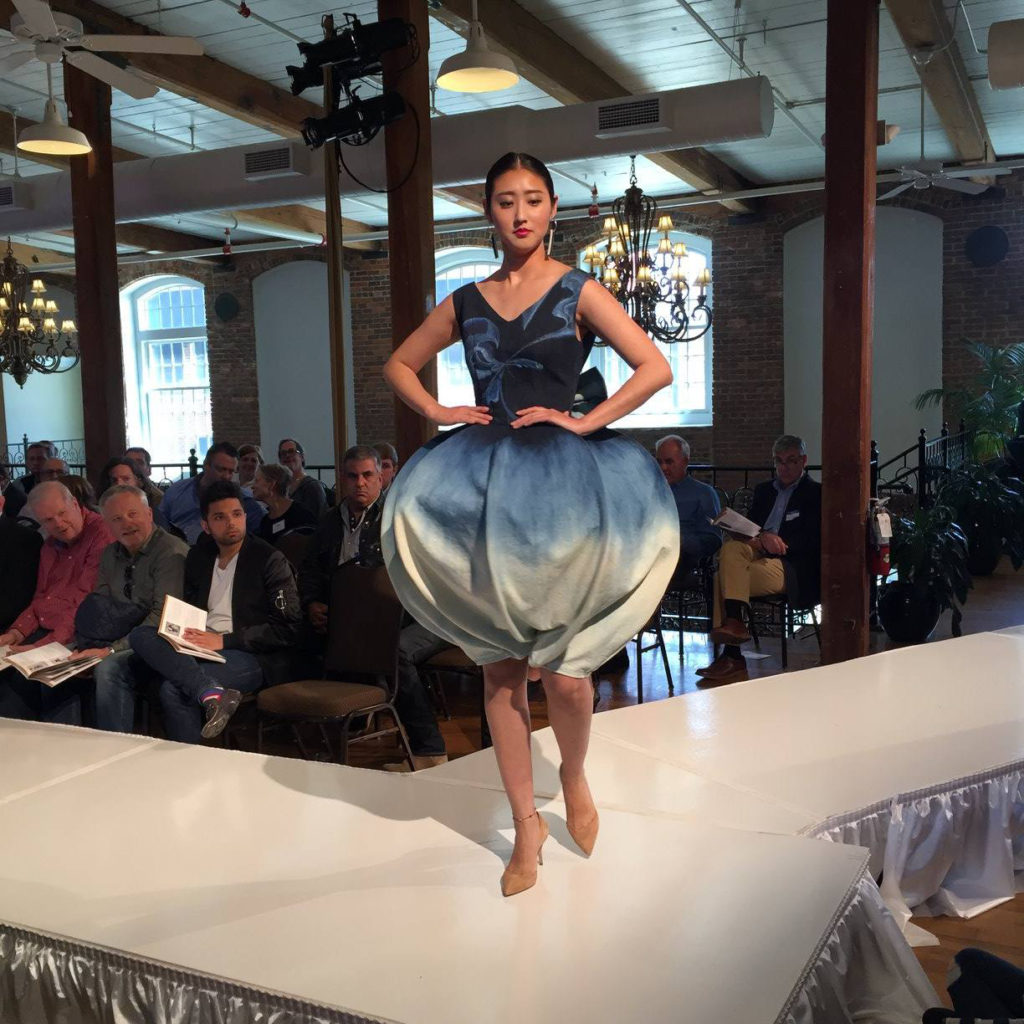 Model on runway wearing a navy blue dress that puffs out at the bottom and fades to light blue and white.