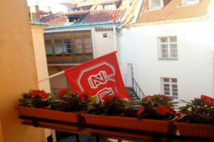 NC State flags from balcony in Prague