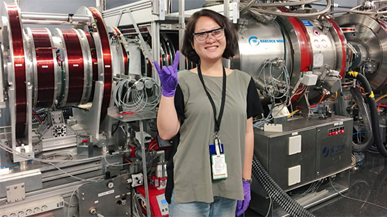Yue Yuan at ORNL, giving the Wolfpack hand gesture wearing purple gloves, in front of heavy lab machinery